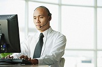 Man with headset, using desktop PC