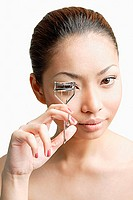 Young woman holding eyelash curler, looking at camera