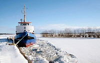 A tug boat at wintertime in the harbour in Västerås, Sweden