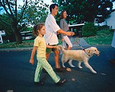 side view of parents with their daughter (6-8) walking the dog