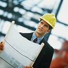 front view of a man wearing a hardhat and holding blueprint