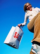 low angle view of a young woman jumping up in the air holding a shopping bag