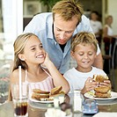 portrait of a father at breakfast with his son and daughter