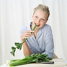 woman biting into a stick of celery