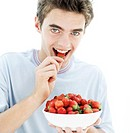 portrait of a young man eating from a bowl of strawberries