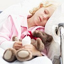 Close-up of a girl (8-10) sleeping in a wheelchair holding her teddy bear