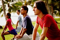 Young adults doing exercises in park.