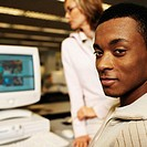 portrait of a young man at a computer station