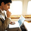 side profile of businessman using laptop in an airplane