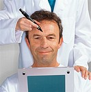 doctor marking a mans face for plastic surgery