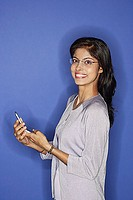 Woman looking at camera, holding mobile phone