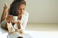 Woman looking at magazine, holding cup and saucer