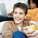 young boy sitting with a bowl of popcorn smiling