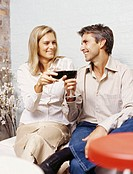mid adult man and a young woman toasting with red wine