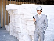 architect holding a mobile phone at a construction site