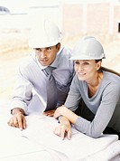 high angle view of two architects wearing hardhats at a construction site