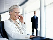businesswoman sitting on a chair and talking on a mobile phone
