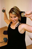 Young woman at the gym, fitness center, doing some exercise with dumb-bells