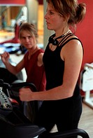 Young woman at the gym, fitness center, walking on the treadmill, controlled by a coach