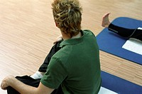 Young man at the fitness studio, gym, sitting on a mat, making gymnastics