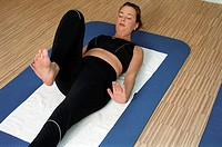 Young woman at the gym, fitness center, doing some gymnastics on a mat, streching (thumbnail)