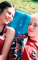 A boy and a girl, a young couple or friends, are sitting on a blue inflatable deckchair in the garden