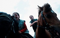 Two girls riding horses, sitting in the saddle, laughing