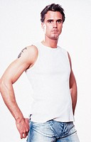 Portrait of a young man, 20-25 25-30 30-35 dark-haired, masculine, powerful, strong, athletic and beautiful in a white sleeveless tee-shirt and jeans