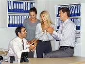 four business executives celebrating with a champagne in an office