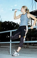 A young athletic woman, 15-20 20-25 25-30 years old, blond, sporty, drinking water (thumbnail)