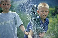 Two children, boys, 5-10 years old, playing in the garden with water