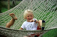 A child, little girl, 5-10 years old, sitting in a hammock in the garden, laughing