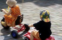 Two children, little boy, little girl, 5-10 years old, playing in the garden, driving a three wheeler and a Bobbycar