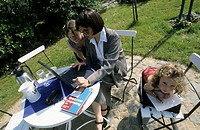 A woman, businesswoman, mother, 40-45 45-50 years old, sitting at the table in the summerly garden, working at the laptop and a two girls, 1-5 5-10 ye...