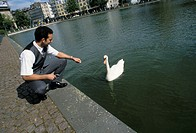 A young man, businessman, 25-30 30-35 35-40 years old, squatting at a pond, feeding a swan