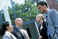 Two young men and two young women, business people, in front of a modern building, office building, talking