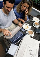 A young man and a young woman, couple, 25-30 30-35 35-40 years old, sitting on a balcony or terrace at a table having breakfast, working at a laptop a...