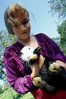 A girl, 5-10 years old, holding a rabbit, bunny, on it's arms