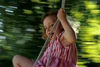 A little girl, 1-5 years old, swinging in the garden in summer