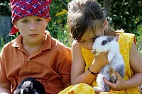 Two children, a boy and a girl, 5-10 years old, in the garden in summer, holding rabbits (thumbnail)