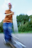 A boy, 5-10 years old, driving a kickboard outside in summer, blurred