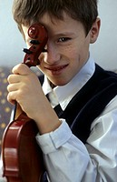A boy, 5-10 years old, holding a violin