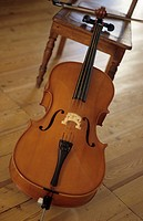 A violoncello leaning against a chair in a room
