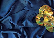 Compact discs lying on a blue cloth