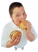 portrait of a young boy (10-14) holding a burger with one hand and eating a burger with the other