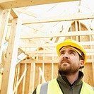 Low angle view of a builder in the middle of a house under construction