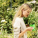 A woman standing in a garden smelling a potted plant