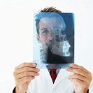 Young male medical professional holding up an x-ray