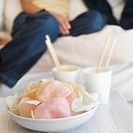 Close-up of assorted prawn crackers in a bowl and chopsticks in cups of noodles