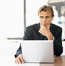 close up front view of businessman sitting at desk with laptop